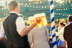 Kellner trägt Masskrüge bei Oktoberfest
