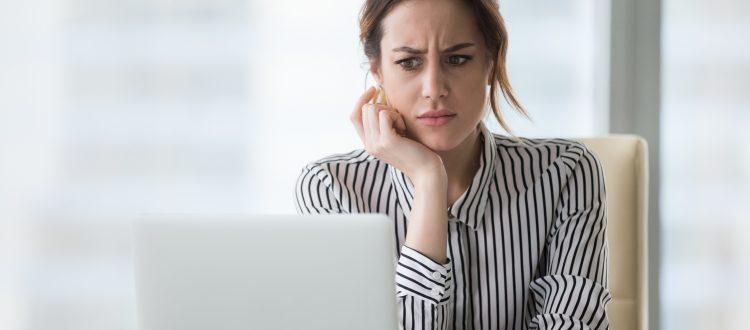 Verzweifelte Frau sitzt an Laptop