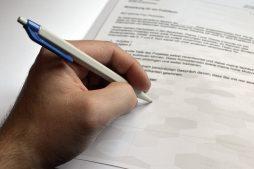 Mann unterschreibt Bewerbungsanschreiben