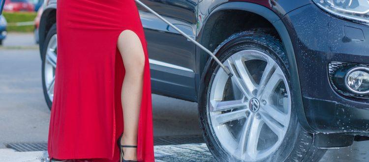 Frau mit rotem aufreizenden Kleid putzt Auto